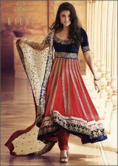 Red anarkali suit with embroidery by Kalki - This red net anarkali suit is beautifully embroidered. The Flare is finished with royal blue embroidery and is paired with red silk churidar and off white antique embroidered dupatta