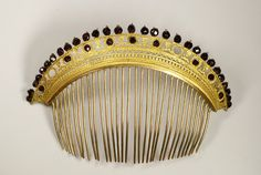 French Empire style comb with garnets (2)  Europe  France  Width : 6 5/8 inch  Height : 4 3/8 inch  Depth : 1/4 inch  Row of garnets along a nice gilt brass frieze with smaller garnets. Gilt silver teeth.
