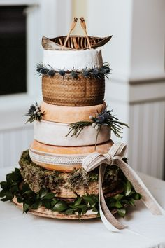 Rustic 6-tier wedding cake with canoe topper | Image by Laura Rowe Photography and Kayla Rocca Photography