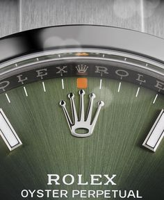 The olive green dial with orange hour marker accents of the Rolex Oyster Perpetual 34. Every Rolex dial is designed and manufactured in-house, largely by hand, to ensure perfection.