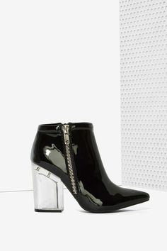 The Truly Bootie is made in black patent leather and features a pointed toe, chunky lucite heel, zipper closure on both sides, and padded rim