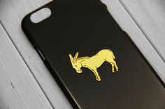 A vintage 24kt gold-plated donkey charm on a hardshell case. - Easy to snap on and allows access to all ports - Slim profile maintains the beauty of your phone - Impact resistant, protects against din