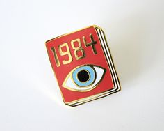 "Wear your book on your sleeve! Big Brother watches you from the cover of George Orwell's dystopian warning, Nineteen Eighty-Four. Based on an original drawing by Jane Mount. She says: ""With the Book Pins, I'm trying to capture the essence of a book in less than an inch square."" This badge is a hard enamel lapel pin with raised gold-plated outlines. It's about 1 inch tall by 0.75 inches wide, and attaches to your clothing with a black rubber clutch. It ships pinned to a small cardboard plaque…"
