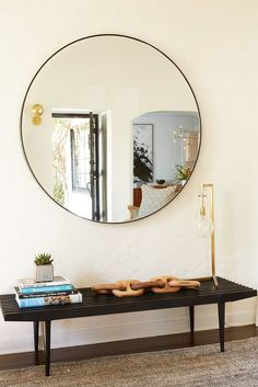 Minimalist entryway with a wooden bench styled with books and a lamp, and a round mirror above
