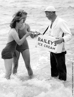 An ice cream vendor wearing waders sells Bailey's ice cream to two women bathing in the sea at Brighton. (Photo by George W. Hales/Fox Photos/Getty Images). 7th August 1939