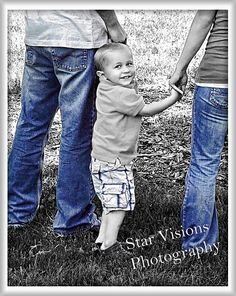 Portrait of two-year-old boy with mom and dad, legs only. Black-and-white with…
