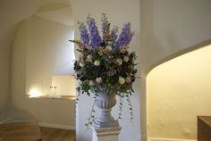 Rustic and textured autumnal flowers styled in an urn in the `Lantern Hall for a Farnham Castle Wedding, designed and created by www.hannahberryflowers.co.uk