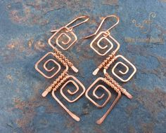 These handmade solid copper earrings are wire wrapped square spirals. Three square shaped spirals are carefully formed out of medium gauge wire and hammered by hand to strengthen and flatten the tails. Then fine gauge wire is used to weave the . Jewelry Making Beads, I Love Jewelry, Metal Jewelry, Jewlery, Jewellery Diy, Yoga Jewelry, Jewellery Making, Wire Wrapped Earrings, Copper Earrings