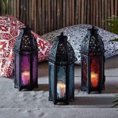 Trio of Black Metal Moroccan Indoor Battery Operated LED Flameless Candle Lanterns with Colored Glass -- Learn more by visiting the image link. (This is an affiliate link) Moroccan Home Decor, Moroccan Lanterns, Moroccan Style, Moroccan Garden, Hanging Candle Lanterns, Led Candles, Paper Lanterns, Glass Candle Holders, Candle Jars