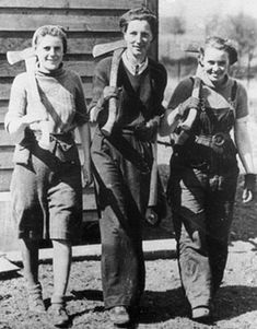 Three Lumberjills off to work with shouldered axes.