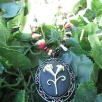 This necklaces features an oval pendant with small red gems spaced around the outer edge and a black center with off white lilies popping out. It is paired with red coral, mother of pearl and black jasper stone chip beads. It is a beautiful piece for a night out, a special occasion or just to dre...