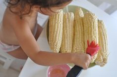 Buttering corn for the grill.  Place corn on one plate, butter or oil in a dish, a brush, and another plate to put the finished product.