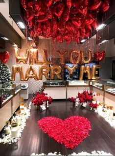"""Megaloons in gold to spell """"will you marry me"""" with 200 x 18"""" red hearts and large hearts either side."""