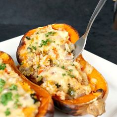 Two halves of roasted butternut squash stuffed with veggie couscous and topped with melted cheese.