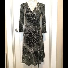 BCBG Paris Faux Wrap Dress, Size XS Flattering faux wrap dress in a classic black and white print.  Excellent used condition.  96% polyester and 4% spandex.  Machine washable.   Length from back of dress to bottom approx 39 inches.  Size XS (0-2) BCBG Paris Dresses Midi
