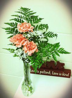 Bud vase, pink carnations, baby's breath, and Leatherleaf
