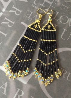 Luxurious long black and gold crystal seed bead earrings made with cream bugle and 11/0 seed beads, crowned with golden shadow a/b Swarovski crystals. The 18 beautiful golden shadow a/b crystals on the fringe are also Swarovski. The french hook earwires are also 14kt gold plated. These