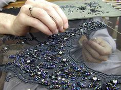 The image above of a craftsman/woman/person working with gold beads on a stretched, sheer fabric is using the tambour technique. Here's a video showing how ...