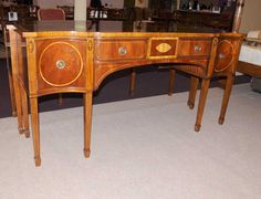 - Stunning George II style sideboard in flame mahogany<BR> - Features elegant inlay work in satinwood including stringing and the classical urn motifs to the top of the legs<BR> - Solid and sturdy piece great for a dining room<BR> - Ample storage with two cupboards and large drawer<BR> - Stylish piece ready to add style to any interior<BR> - We have various tables and chairs to match if you are looking for a complete dining set<BR> - Offered in great shape...