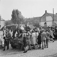 Dutch civilians crowd around jeeps and scout cars of XXX Corps in Grave - south-west of Nijmegen - after the British had linked up with the US 82nd Airborne Division, 19 September