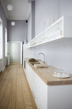 White and wood kitchen with gray, butcher block counters, open shelving