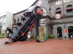 041 - Em Gramado, no Mundo a Vapor em frente a Locomotiva, que é a representação de um acidente na Estação de Montparnasse na França em 1895.