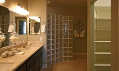 Your bathroom in the 1700-golf model.  The glass enclosed walk in show and the double sinks give you plenty of room.  Notice the built in linen closet right off the bathroom.  The built in combined with the large cabinets under the sink will give you plenty of storage space.  Pictured:  1700-golf model  Sunland Springs, Mesa, AZ