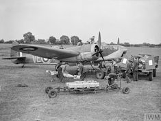 Bristol Blenheim Mark IV, R3600, of No. 110 Squadron RAF, undergoes an elaborate servicing for the photographer at RAF Wattisham, Suffolk. Armourers unload 250-lb GP bombs and Small Bomb Containers (SBCs) of incendiaries from a trolley, while other groundcrew refuel the aircraft and attend to the engines, the cockpit and the gun-turret, accompanied by a pet dog on the engine cowling.