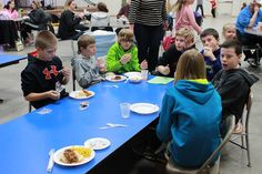 A few young volunteers enjoy a well-deserved meal with friends at the Peace Lutheran Church in Waverly, NE.  Volunteers spent the day cleaning, painting, and landscaping the grounds of the church.