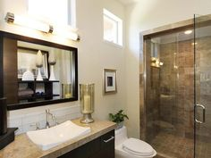 Glass Shower Guest Bathroom: An enlarged shower dresses up this guest bathroom with earthy tones and clean lines. Soft light pours into the space from the two smaller windows located above eye-level.  From HGTVRemodels.com