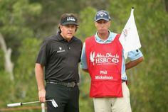 Phil Mickelson of the USA chats with his caddie Jim -Bones-MacKay on the 11th hole during the final round of the Abu Dhabi HSBC Golf Championship at the Abu Dhabi Golf Cub on January 19,2014