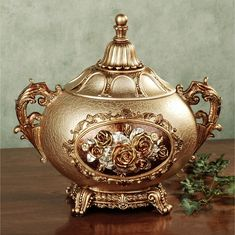 """With its ornamental style, the Golden Rose Covered Jar will make a stunning statement wherever it is placed. Resin accent has a handpainted, champagne gold, crackle-style finish and is adorned with golden handles, a rose bouquet medallion in the center, and ornate base. Decorative covered jar is 13""""Wx9""""Dx11.5""""H.    • Extravagant covered jar with elegant scroll handles  • Lid is removable  • Search G987 for the Golden Rose Candleholders"""