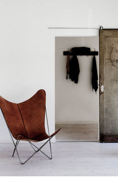 Butterfly chair, white walls, pocket doors