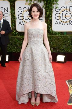 Golden Globes 2014: Red Carpet Arrivals.  Michelle Dockery, star of best television series nominee Downton Abbey, poses in a strapless, jewel-adorned gown.