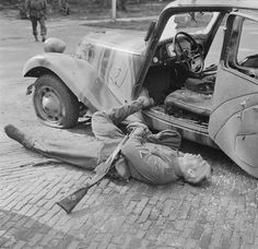 A German private killed in action by British Bren gun fire near his car at a crossroads in Belgium during Operation Market Garden - September 1944
