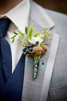 A boutonniere with an acorn, a freesia bud, privet berries, and seeded eucalyptus | Brides.com