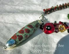 Poppy Dreams Necklace featuring lampwork by Glass Junkies and Mermaid Glass; various seed bead spiral ropes and wirework.  Honey from the Bee