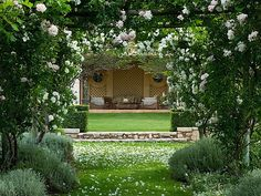 provence, france - designer dominique lafourcade. Wooden pergola with climbing white rose leading to seating area