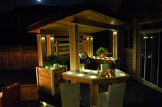 "A luxurious outdoor kitchen, sheltered by a sloped roof, with generous counter space and built-in bar.  The counters are white acrylic and lit from below for a cool glow.  From ""Decked Out"" project ""The Lounge Deck"".  Deck Design by Paul Lafrance Design."