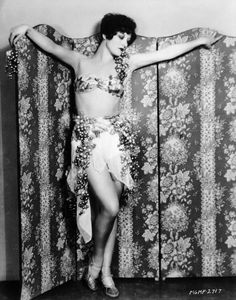 Wearing a two piece swimsuit draped with grapes film star Joan Crawford drapes her arms across an ornately patterned screen 1928