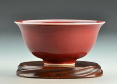 """A Chinese Strawberry Glazed Porcelain Bowl having a short footrim and bearing a six-character mark in underglaze blue, raised on carved hardwood stand, porcelain measures 4.875""""W x 2.25""""H."""