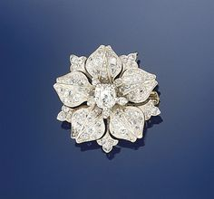 A late 19th century diamond brooch  Modelled as a flowerhead, the central cushion shaped old brilliant-cut diamond with old-cut diamond point stamen detail to an old-cut diamond petal surround with trefoil detail, circa 1890