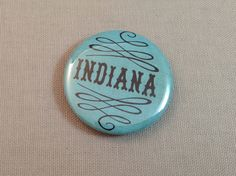 Blue Indiana Bottle Opener. We love this simple bottle opener! Features the word Indiana and pretty filigree. This little guy can slide onto a keychain, fit in your pocket, or hang out in your purse!