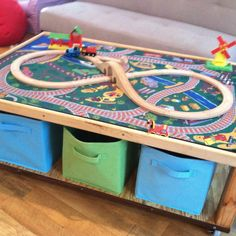 Well my dad made this great train table for my son. With my idea to build it around a 10 rug I found at TRU. It's got caster wheels that will lock so it can be immobile if you want. Storage on the bottom for 6 of those square cubes from Target!