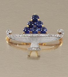 "ROCK CRYSTAL, SAPPHIRE AND DIAMOND ""FRUIT BOWL"" BROOCH, CARTIER, CIRCA 1915.  Designed by Charles Jacqueau, the carved rock crystal fruit bowl lined with millegrain-set circular-cut diamonds and embellished with fruit of sapphire beads, signed Cartier, French assay marks."