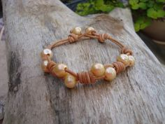 The ABBY bracelet is shown here in natural leather. This bracelet features four sets of 7mm golden freshwater pearls knotted on leather cord with two more serving as button closures. This bracelet fits the regular sized wrist (7- 7 1/4), but can be made any size for no extra charge.  This bracelet comes in black, brown,antique brown, or natural and will look great with any outfit!  Desired and collected for nearly 4,000 years, pearls were worn by the wealthy and served as the royal symbo...