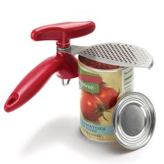 """Manual can opener with attached strainer. 7 2/3"""" L x 4"""" W x 2 1/3"""" H. Hand wash only. Stainless steel, plastic. Imported."""
