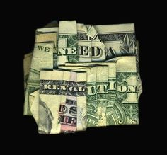 """New Orleans-based artist Dan Tague folds a dollar bill as many as 100 times, until it spells out an unexpected phrase, including """"We Need A Revolution"""" and """"Trust No One""""."""