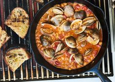 You can cook clams right on the grill grate, but getting a skillet involved means capturing all of their delicious briny juices. Don't forget to grill some bread for that same reason.