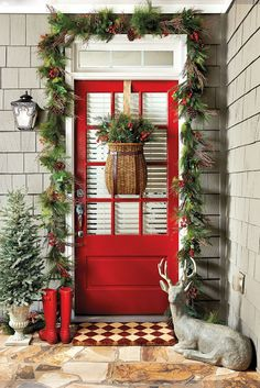 """Red door decked out with red-berried pine garland and fishing basket filled with greenery as a """"wreath"""""""